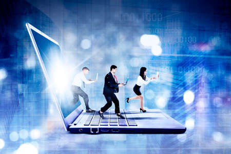 Three business people using a laptop while running and getting out from laptop screen with cyberspace background Zdjęcie Seryjne