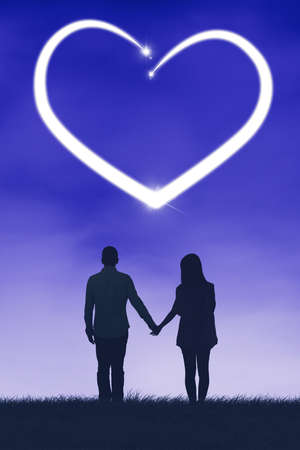 Silhouette of romantic couple holding hands together while standing and looking at a heart symbol shaped light with stars on the night sky Zdjęcie Seryjne