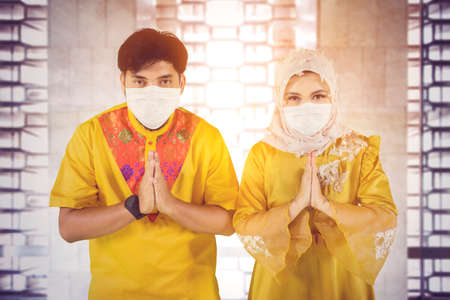 Muslim young couple wearing face mask while showing congratulate hands gesture Eid Mubarak and standing together in the mosque