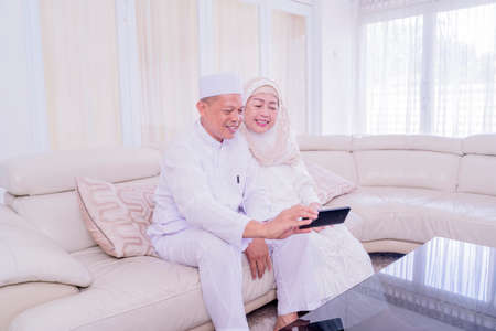 Happy Muslim aged couple doing video call with their family on a mobile phone during Eid Mubarak while sitting in the living room at home Zdjęcie Seryjne