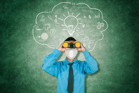Businessman wearing face mask while using binoculars and standing with light bulb over his head on chalkboard background