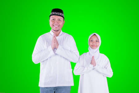 Little girl with her father showing congratulate hands gesture Eid Mubarak while standing together in the studio with green screen background Zdjęcie Seryjne