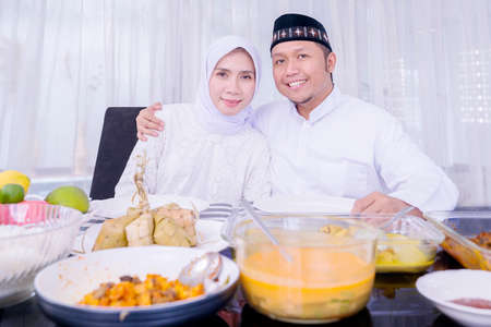 Muslim young couple smiling at the camera while having dinner together during Eid Mubarak in dining room at home Zdjęcie Seryjne