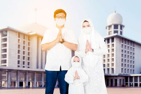 Happy muslim family wearing face mask while showing congratulate hands gesture Eid Mubarak and standing with mosque background