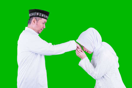 Muslim woman apologizing to her husband during Eid Mubarak while handshaking in the studio with green screen background