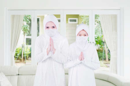 Little girl with her father wearing face mask while showing congratulate hands gesture Eid Mubarak and standing in the living room at home
