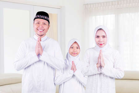 Happy Muslim family showing congratulate hands gesture Eid Mubarak while standing together in the living room. Shot at home