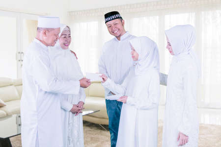 Three generation happy muslim family giving money envelope to little girl while standing in the living room during Eid Mubarak at home Zdjęcie Seryjne