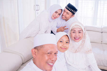 Three generation happy muslim family taking selfie photo together by using smartphone while celebrating Eid Mubarak in the living room. Shot at home