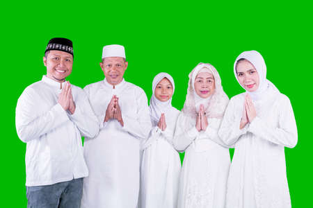 Three generation Muslim family showing congratulate hands gesture Eid Mubarak while standing together in the studio with green screen background Zdjęcie Seryjne