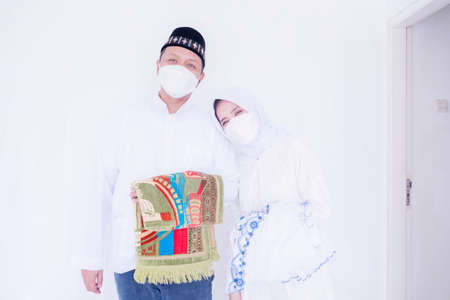 Happy Muslim young couple wearing face mask while carrying prayer rugs during ready to congregation prays Zdjęcie Seryjne