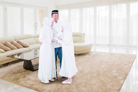 Muslim little girl getting money envelope from her parents at Eid Mubarak while standing together in living room at home