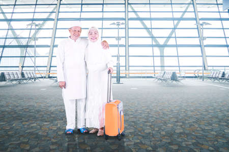 Muslim elderly couple holding a luggage while smiling at the camera and standing in the airport