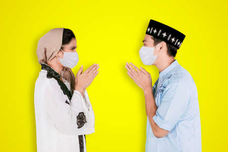Muslim young couple wearing face mask while forgiving to each other during Eid Mubarak and standing together in the studio with yellow background