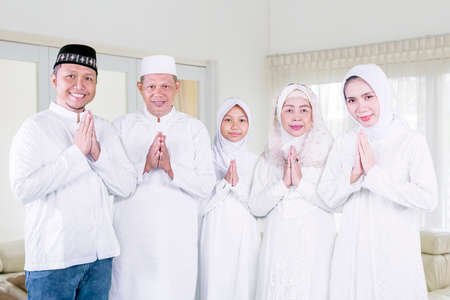Three generation Muslim family showing congratulate hands gesture Eid Mubarak while standing together in the living room. Shot at home