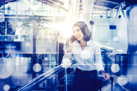 Double exposure of businesswoman making a phone call while standing with blurred light sparkles background
