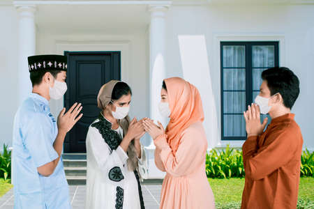 Four young people wearing face mask while give greet hands to forgive each other during Eid Mubarak celebration in the house yard Zdjęcie Seryjne