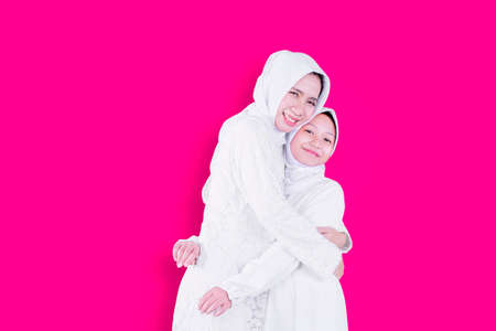 Happy Muslim mother embracing her daughter while standing in the studio with pink background Zdjęcie Seryjne