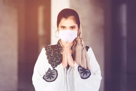 Muslim young woman wearing face mask while showing congratulate hands gesture Eid Mubarak and standing with mosque background