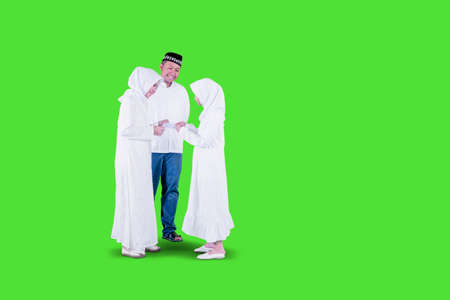 Muslim little girl getting money envelope from her parents while standing in the studio at Eid Mubarak. Shot with green screen background Zdjęcie Seryjne