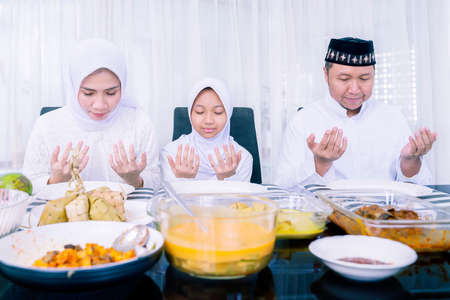 Happy Muslim family praying together before having dinner in dining room at Eid Mubarak. Shot at home