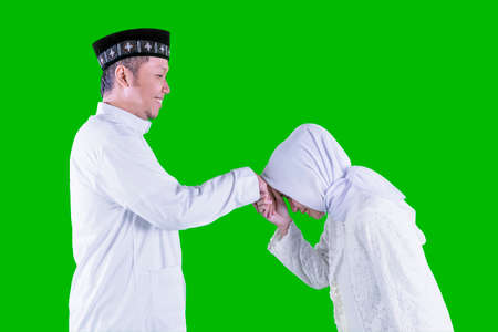 Side view of young Muslim man handshaking with his wife and forgiving to each other during Eid Mubarak in the studio with green screen background