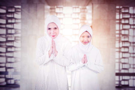 Little girl with her mother showing congratulate hands gesture Eid Mubarak while standing together in the mosque with sunlight background