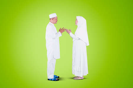 Side view of Muslim old couple handshaking and forgiving to each other during Eid Mubarak in the studio with green screen background