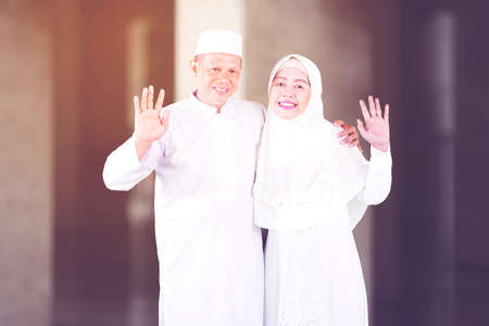 Smiling Muslim senior couple waving hands at the camera and standing together in the mosque