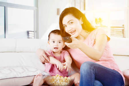 Happy mother enjoying watches television with her daughter while sitting on the couch and eating popcorn at home