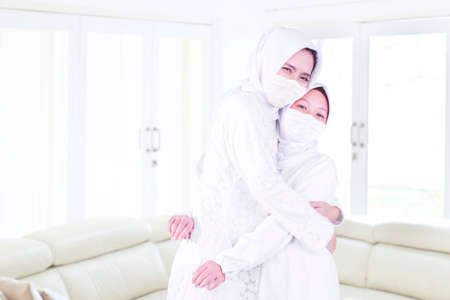 Muslim little girl wearing face mask while embracing her mother in the living room at home