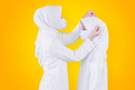 Muslim young mother wearing face mask while tidying veil of her daughter in the studio with yellow background