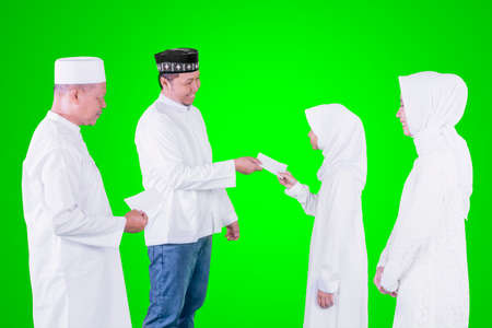 Muslim little girl getting money envelope from her father and grandfather while standing with her mother during Eid Mubarak in the studio with green screen background Zdjęcie Seryjne