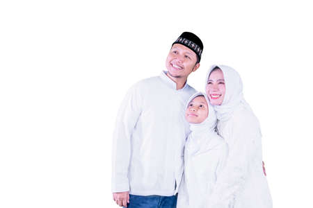 Happy Muslim parents hugging their daughter and looking at the copy space while standing together in the studio, Isolated on white background Zdjęcie Seryjne