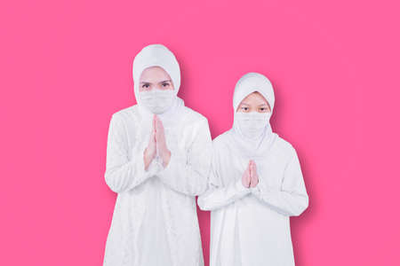Young mother and her daughter wearing face mask while showing congratulate hands gesture Eid Mubarak and standing together in the studio
