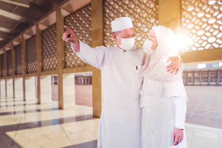 Muslim elderly couple wearing face mask while pointing something and standing in the mosque with sunlight background