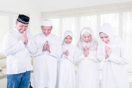 Happy three generation muslim family showing a greeting hands while standing together during Eid Mubarak in the living room at home Zdjęcie Seryjne