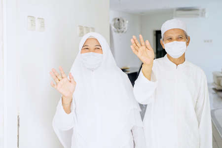 Muslim elderly couple wearing face mask while waving hands at the camera and doing quarantine at home during Eid Mubarak