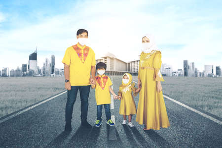 Muslim parents wearing face mask while holding hands their children and standing on the road with mosque background