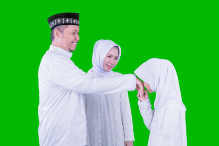 Muslim little girl apologizing to her parents during Eid Mubarak while handshaking in the studio with green screen background