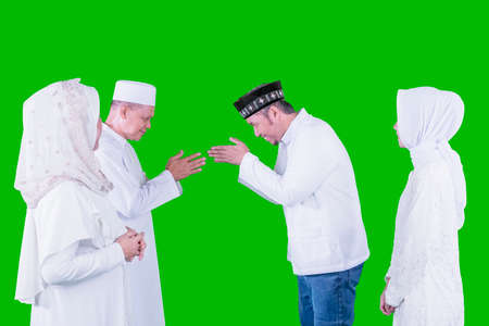 Happy Muslim man showing congratulate hands gesture Eid Mubarak to his parents while standing with his wife in the studio with green screen background Zdjęcie Seryjne