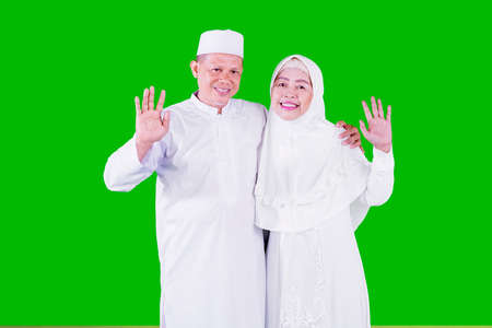 Happy Muslim old man embracing his wife while waving hands at the camera and standing in the studio with green screen background