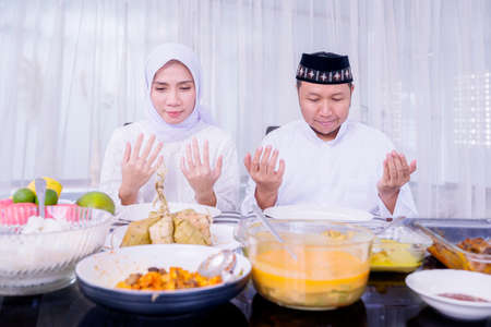 Muslim young couple praying together before having dinner in dining room at Eid Mubarak. Shot at home