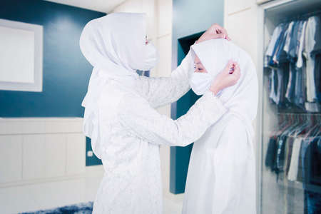 Muslim young mother wearing face mask while tidying veil of her daughter in the wardrobe room