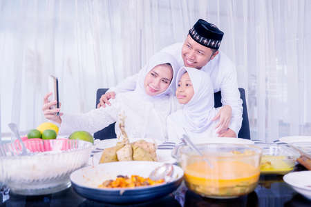 Happy Muslim family using a smartphone to taking a selfie photo together during Eid Mubarak in dining room. Shot at home