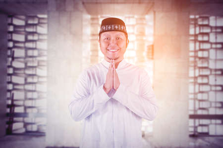 Muslim young man showing congratulate hands gesture Eid Mubarak while smiling at the camera in the mosque