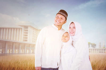 Happy Muslim parents hugging their daughter while standing together in the mosque yard
