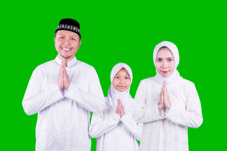 Happy Muslim family showing congratulate hands gesture Eid Mubarak while standing together in the studio with green screen