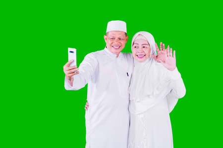 Smiling Muslim aged couple doing video call with their family on a mobile phone during Eid Mubarak while standing in the studio with green screen background Zdjęcie Seryjne