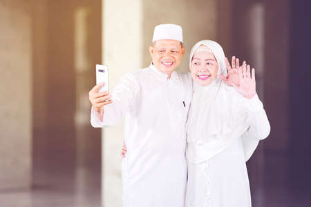 Happy Muslim old couple doing video call with their family on a mobile phone during Eid Mubarak while standing in the mosque Zdjęcie Seryjne
